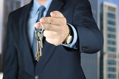 Business attorney gives entrepreneur keys to a new office after reviewing a lease